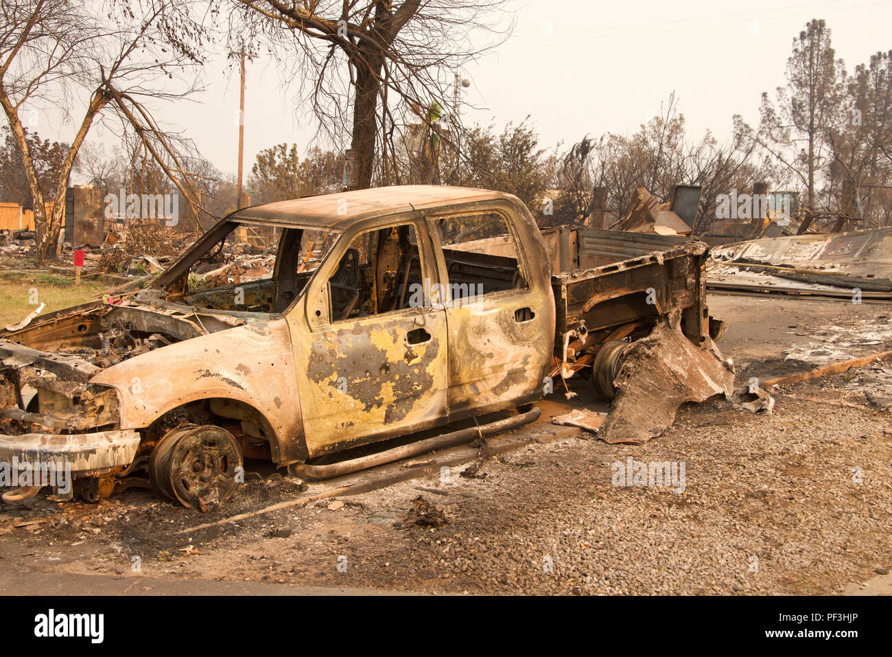 Charred truck in front of home burned to the ground in the recent wild fire fire storm in Redding, California. Smoke and ash in the air as the fire co - Stock Image