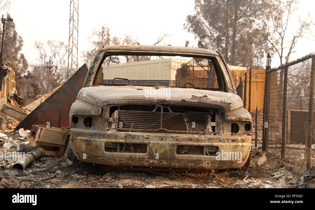 Charred car next to chain link fence in front of home burned to the ground in the recent wild fire fire storm in Redding, CA. Smoke and ash in the air - Stock Image