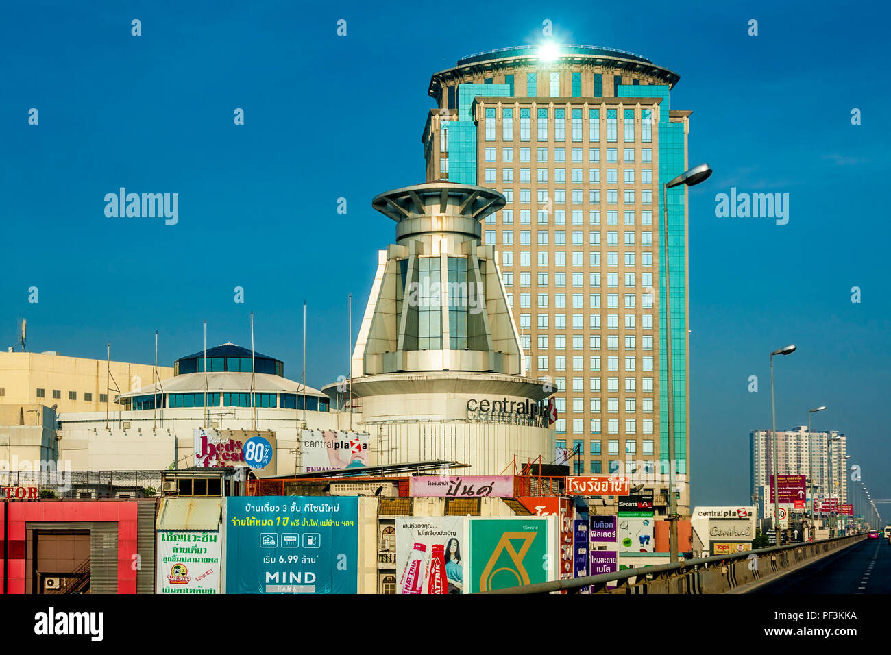 One big highlight on the top of one of Bangko's buildings close to the freeway. Clear blue sky. - Stock Image