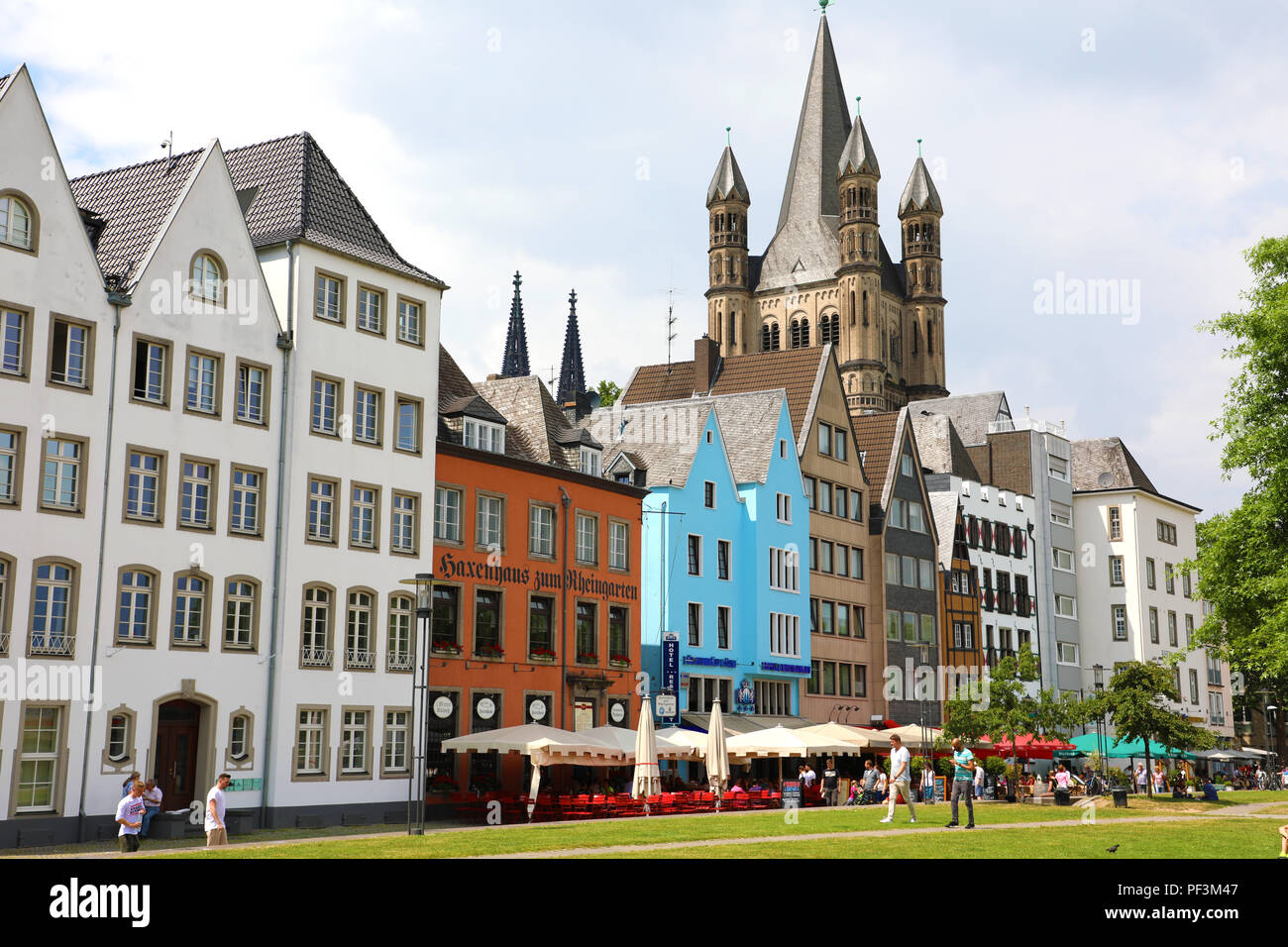 COLOGNE, GERMANY - MAY 31, 2018: houses and park in Cologne, Germany. Many of them are colourful, they are facing a public park with green grass and s - Stock Image