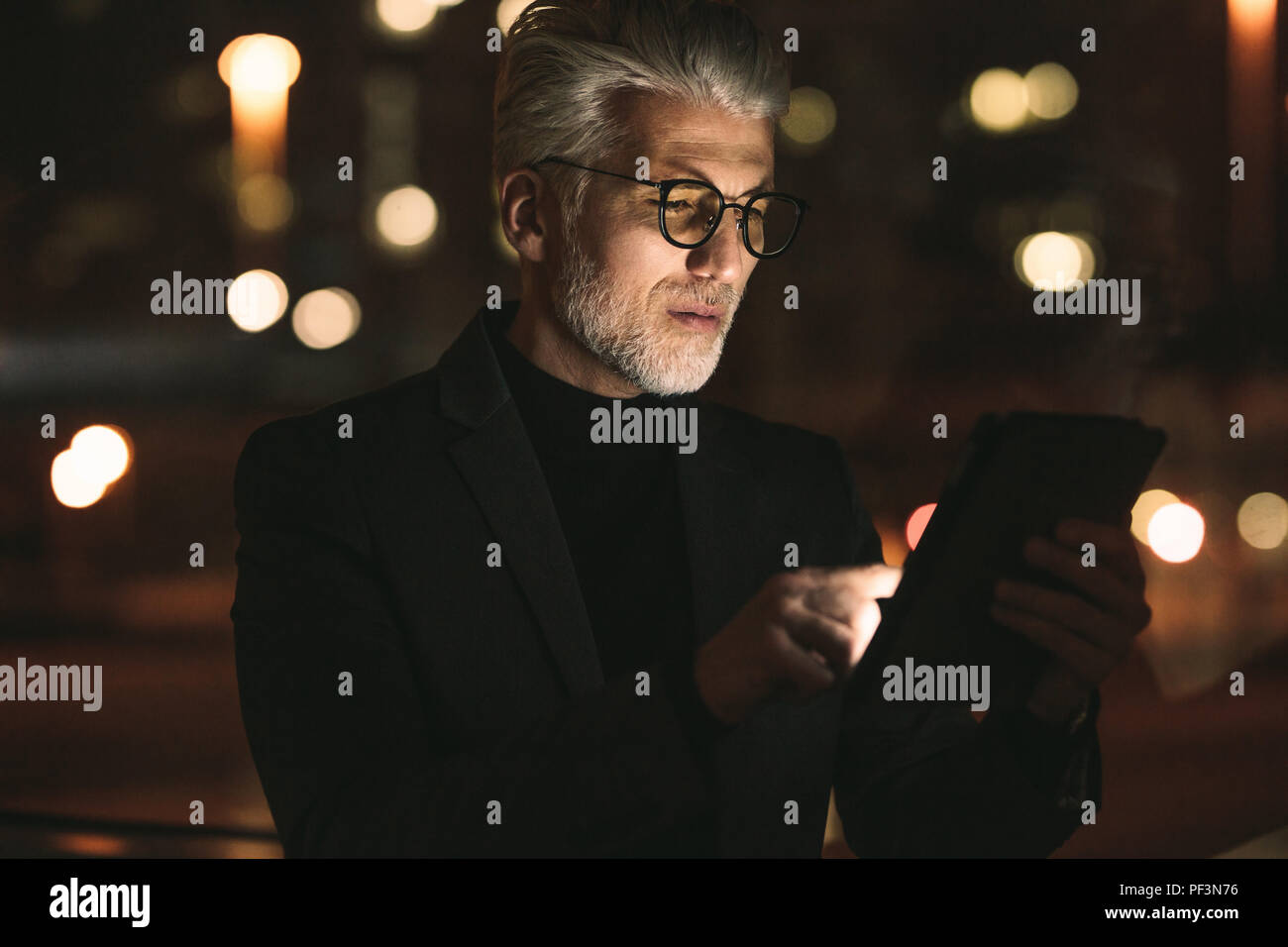 Senior business associate working on tablet computer late night in office. Mature man working overtime in office. Stock Photo