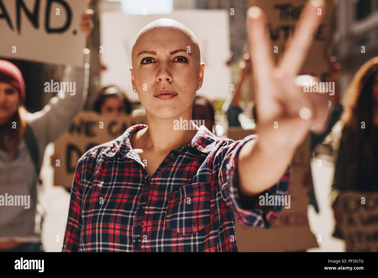 Bald woman protesting outdoors and showing a peace hand sign. Woman with group of people protesting outdoors on city street. - Stock Image