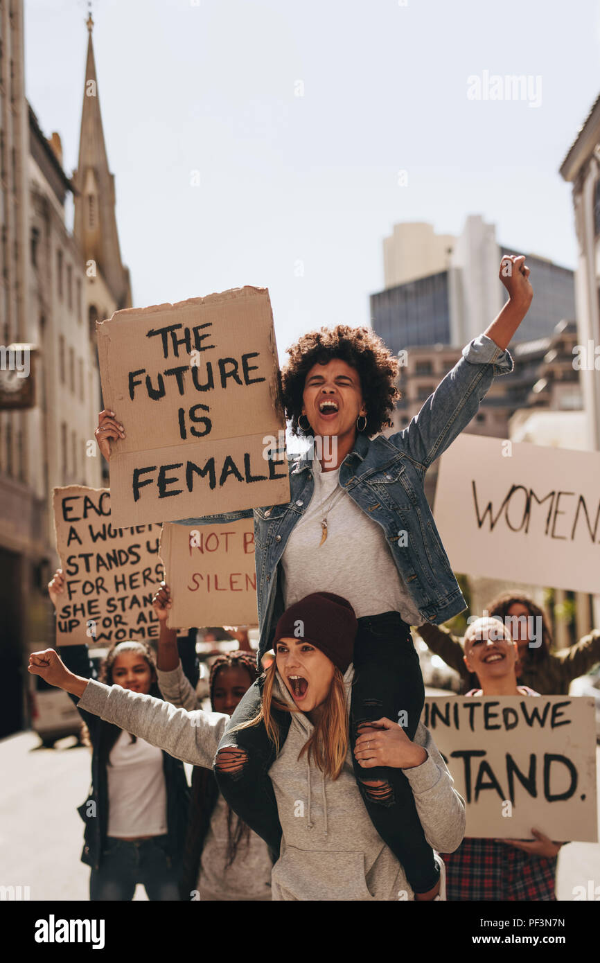 Group of aggressive protesters marching on the road with signboards. Women holding protest signs for female future and empowerment. - Stock Image