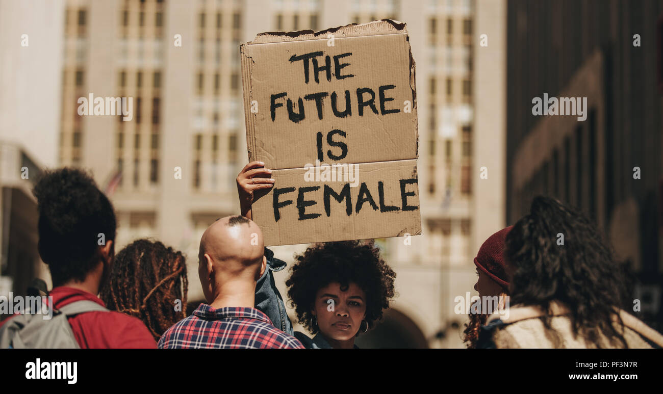Woman's march protest sign that reads the future is female. Female walking on the city street holding a banner with group of people. - Stock Image