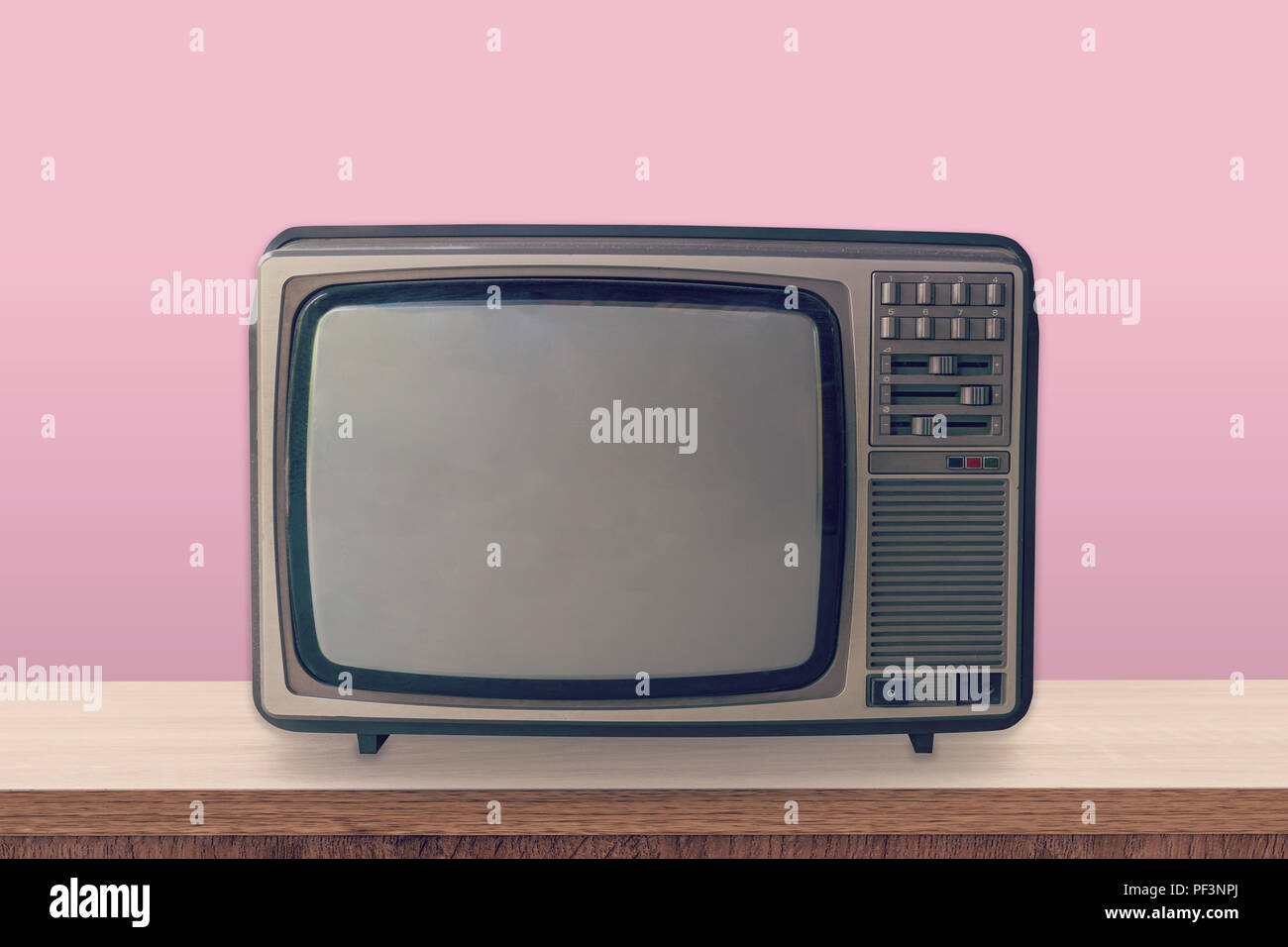 Vintage TV box on wooden table and pink pastel color background. - Stock Image