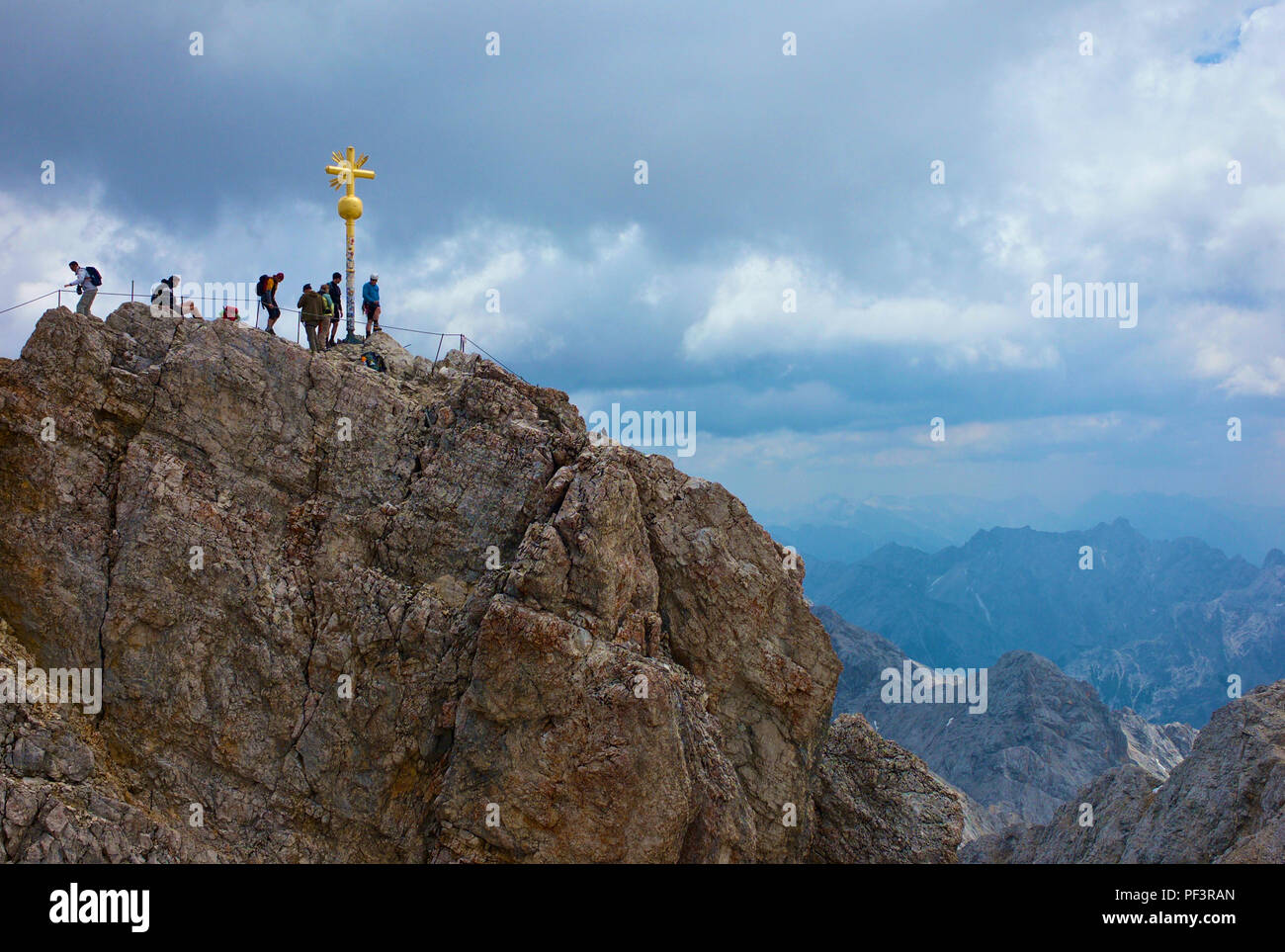 Bergwanderer auf dem Zugspitzgipfel. Alpenpanorama und Gipfelkreuz. - Stock Image