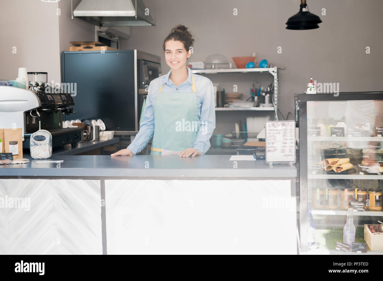 Smiling Shopkeeper Behind Counter - Stock Image