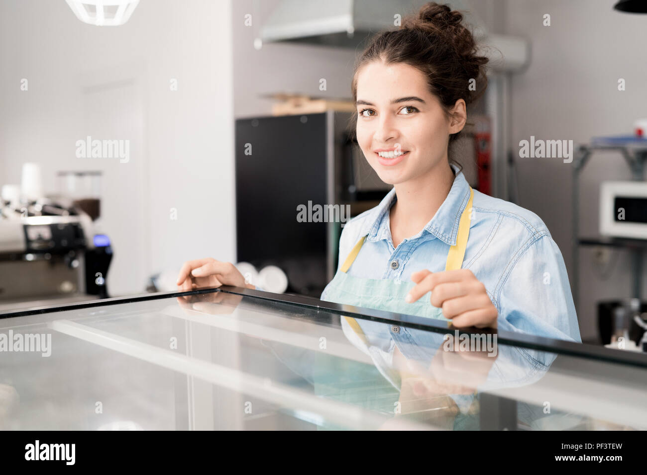 Smiling Woman Working in Cafe - Stock Image