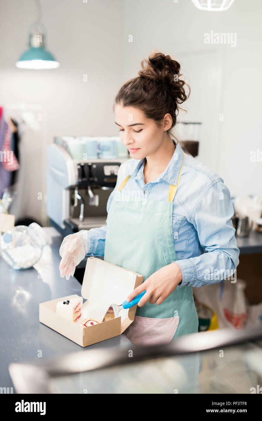 Woman Packing Cakes to Go in Cafe - Stock Image