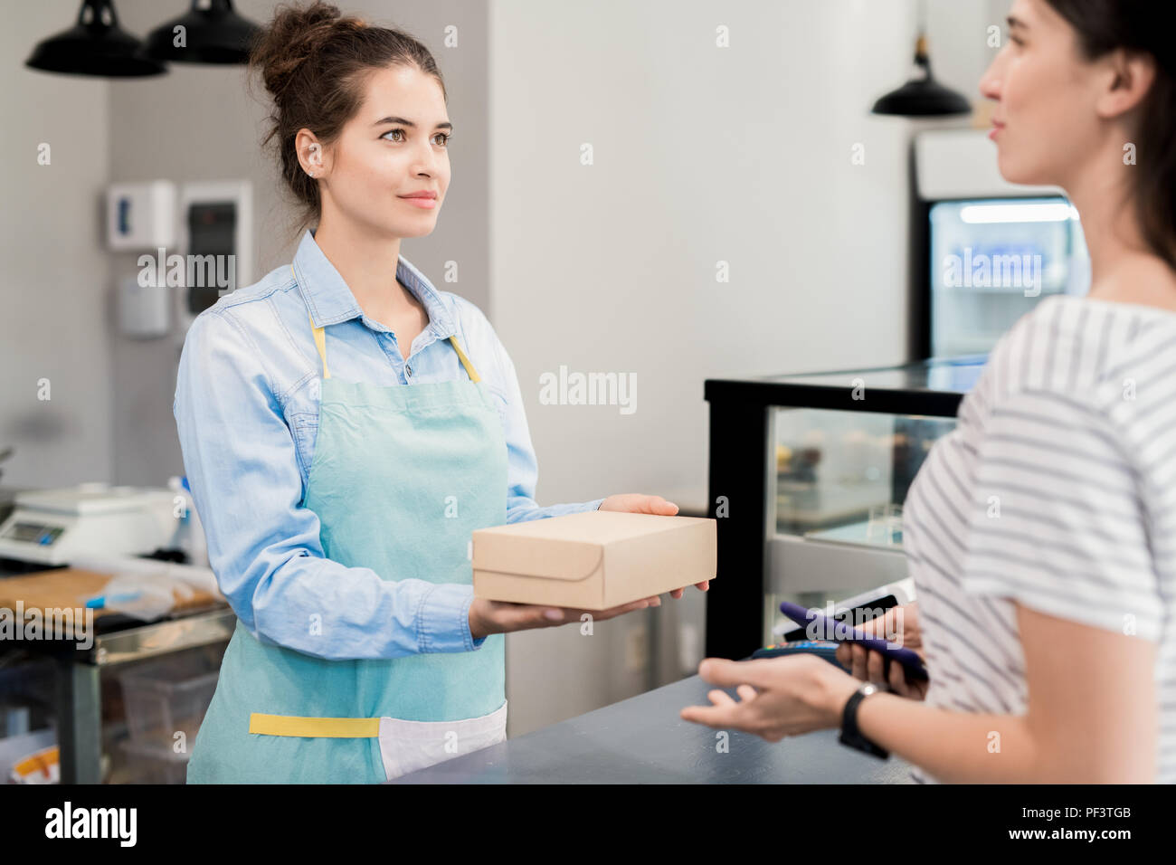 Shopkeeper Handing Box to Customer - Stock Image