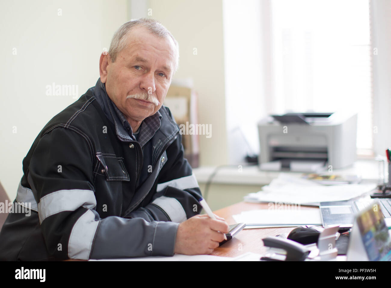 Belarus, Gomel, April 24, 2018. Reception point. Elderly employee at a table in the office.Foreman commander - Stock Image