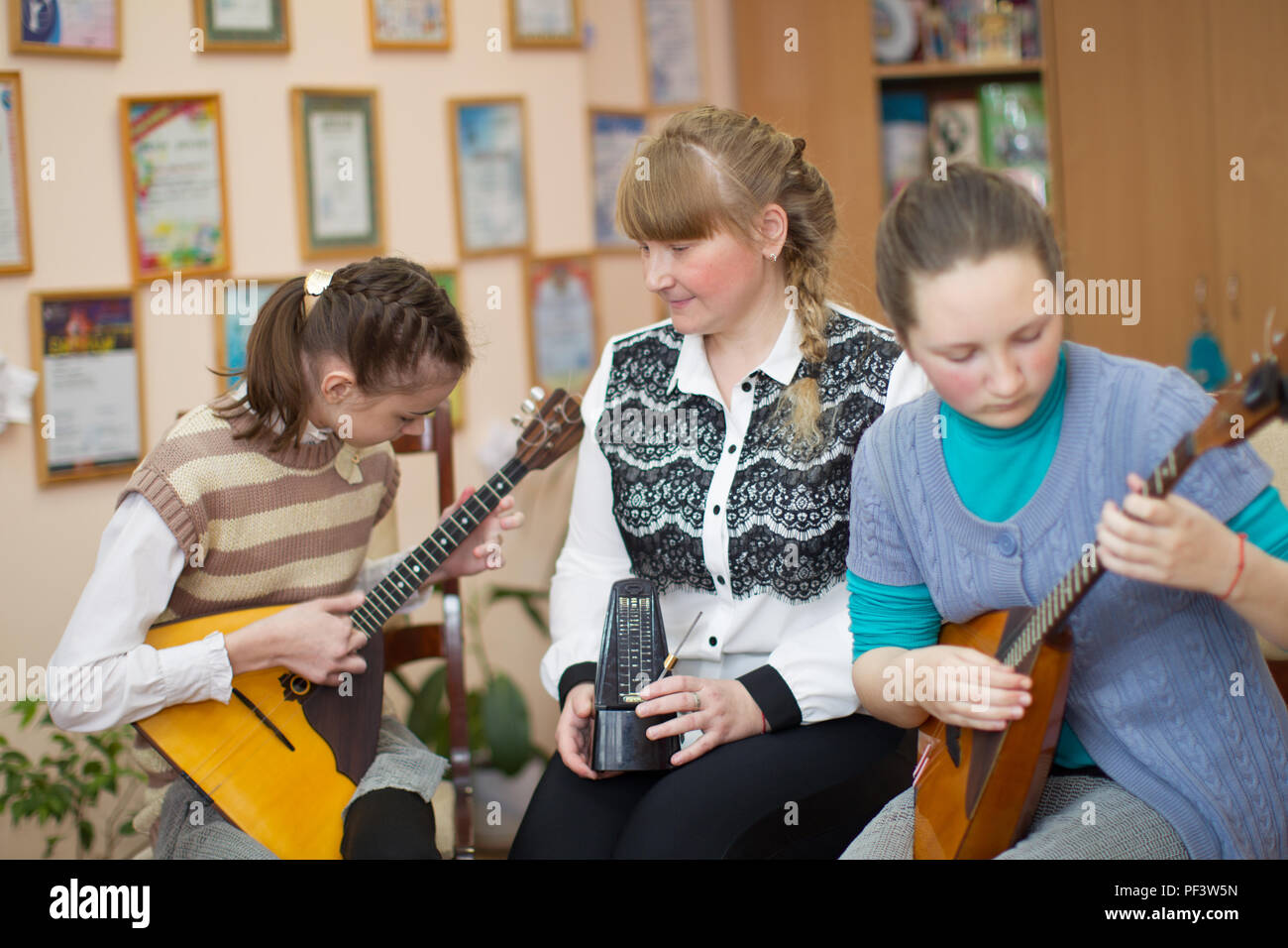 Belarus, Gomel, April 24, 2018. Children's music school. Open music lesson. The teacher of music teaches to play girls on a balalaika - Stock Image
