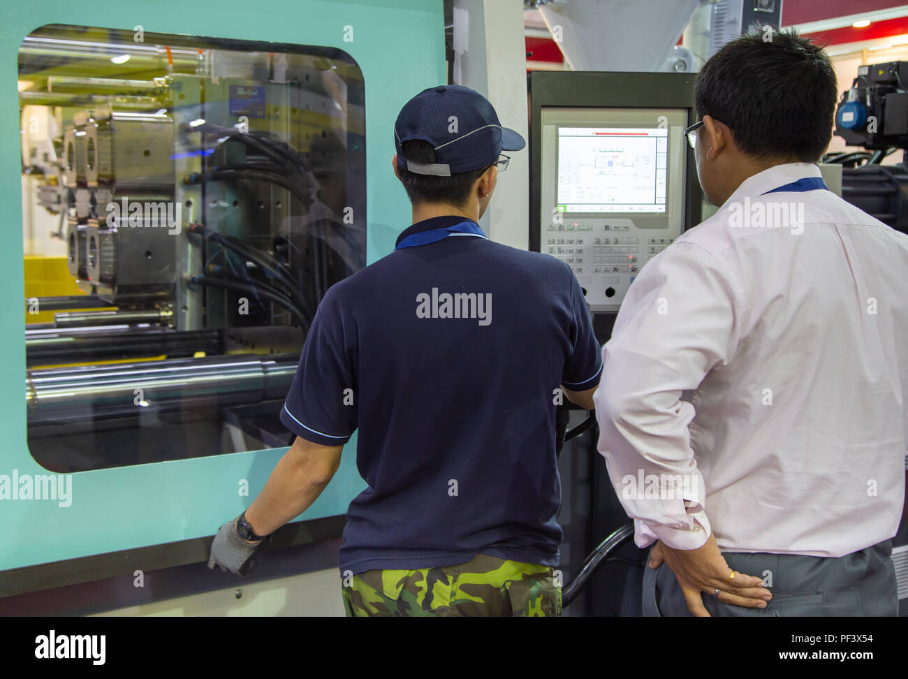 worker operate industrial plastic injection molding press machine for manufacturing - Stock Image