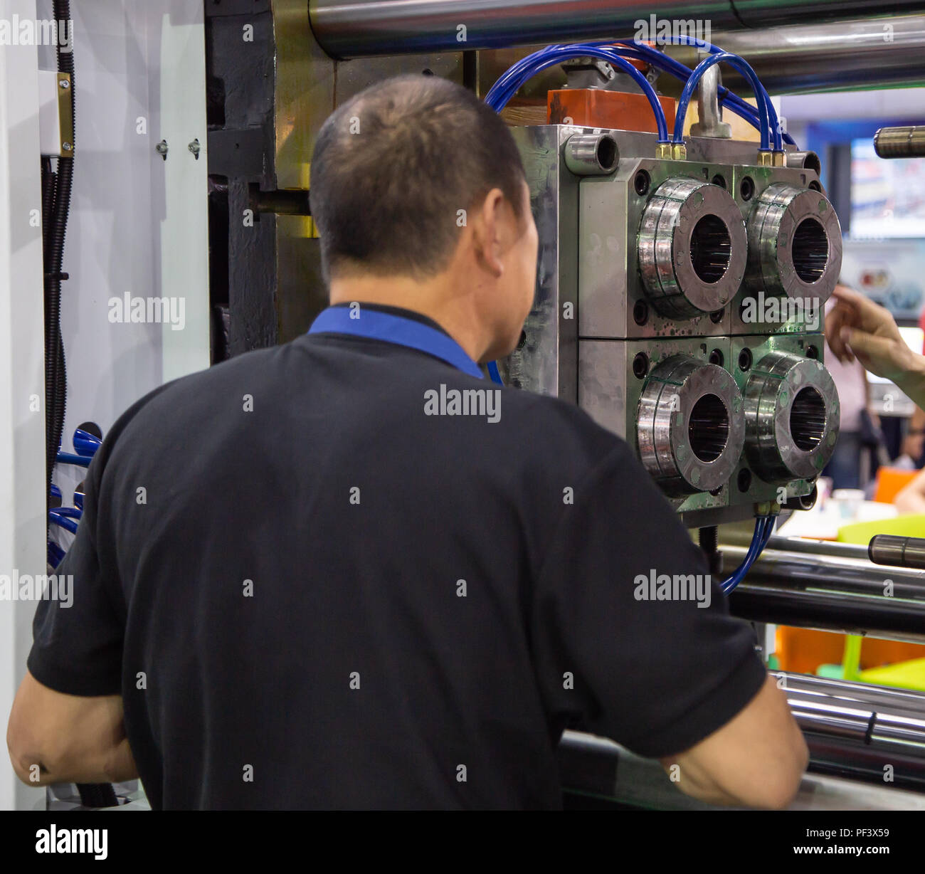 worker setting up industrial plastic injection molding press machine for manufacturing - Stock Image