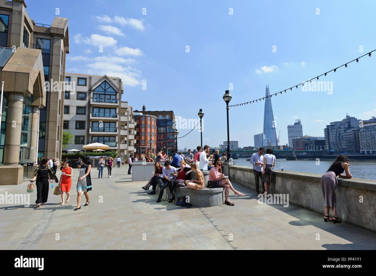 People enjoying the hot British weather relaxing by the Thames river bank, London, England, UK - Stock Image