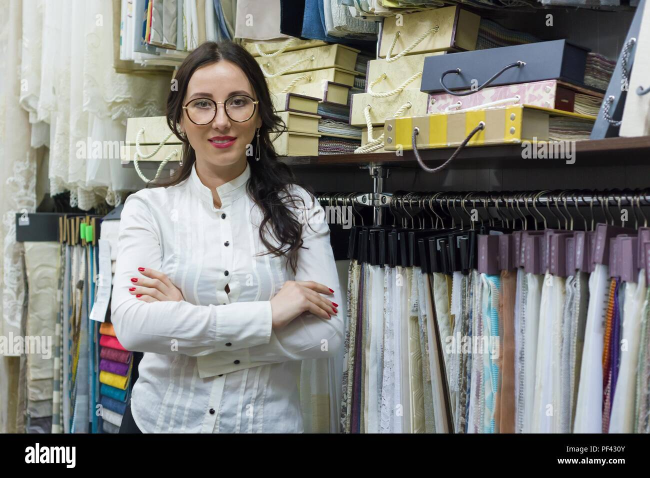 Portrait of happy woman owner with crossed arms in interior fabrics store, background fabric samples. Small business home textile shop - Stock Image
