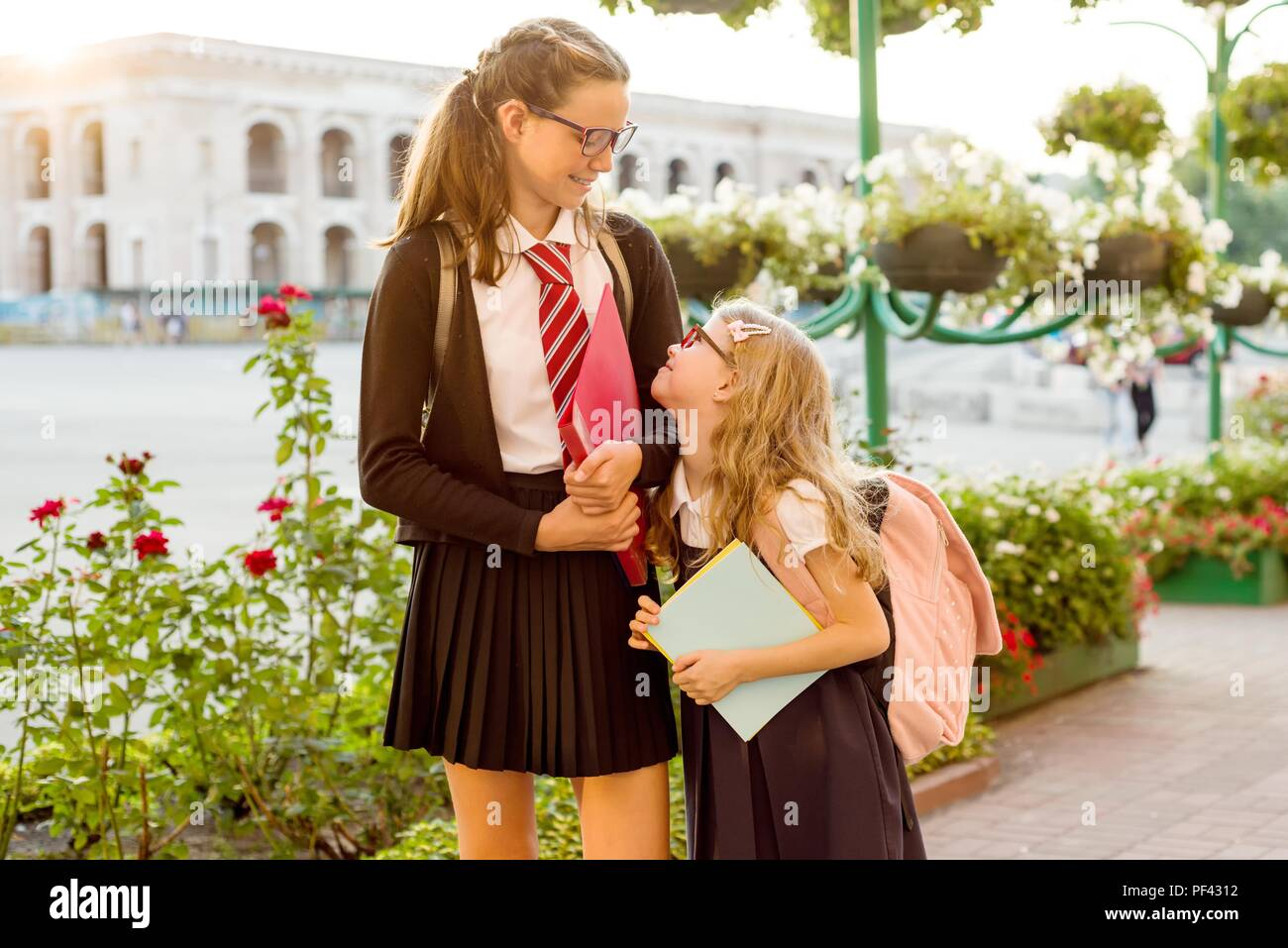 Outdoor portrait of two girls. A high school student and an elementary school student  go to school. - Stock Image