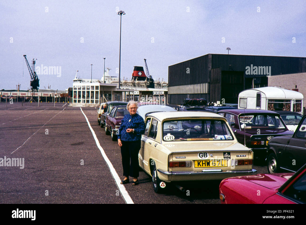 A snapshot of a woman stood next to a Triumph 1500 car whilst waiting for a ferry in the 1970s - Stock Image