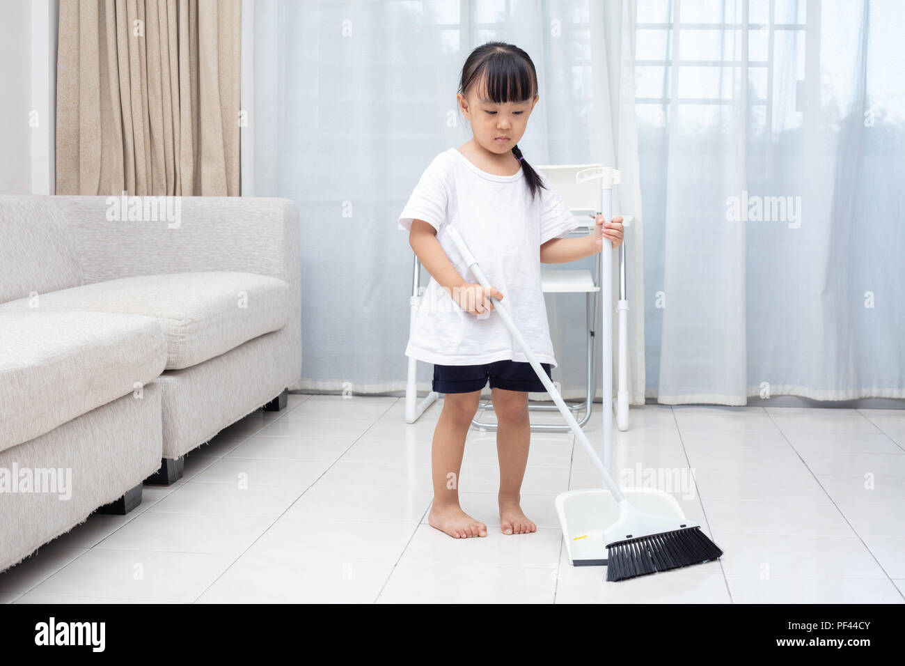 Asian Chinese little girl helping doing cleaning with broom and dustpan at home - Stock Image