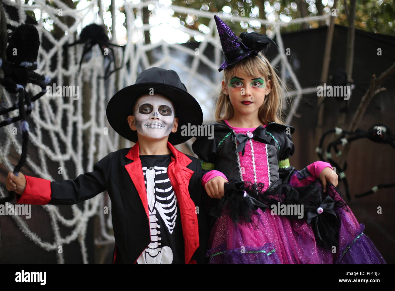 Halloween kids, Trick-or-treat. Kids wears costume of skeleton and witch for Halloween trick-or-treating party - Stock Image
