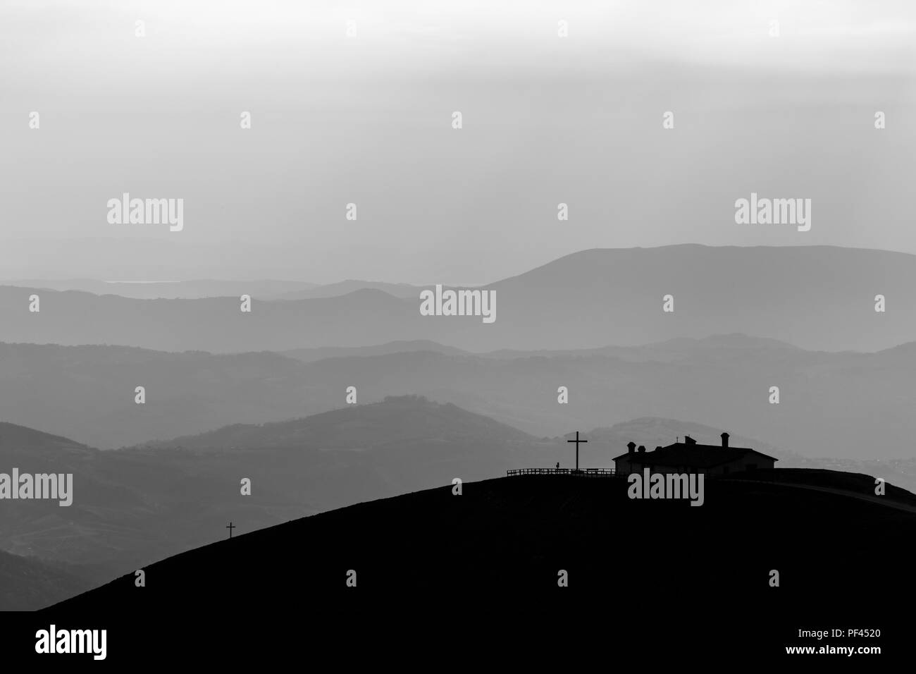 View of Serrasanta hermitage (Umbria, Italy) on top of a mountain, with various others mountains layers in the background - Stock Image