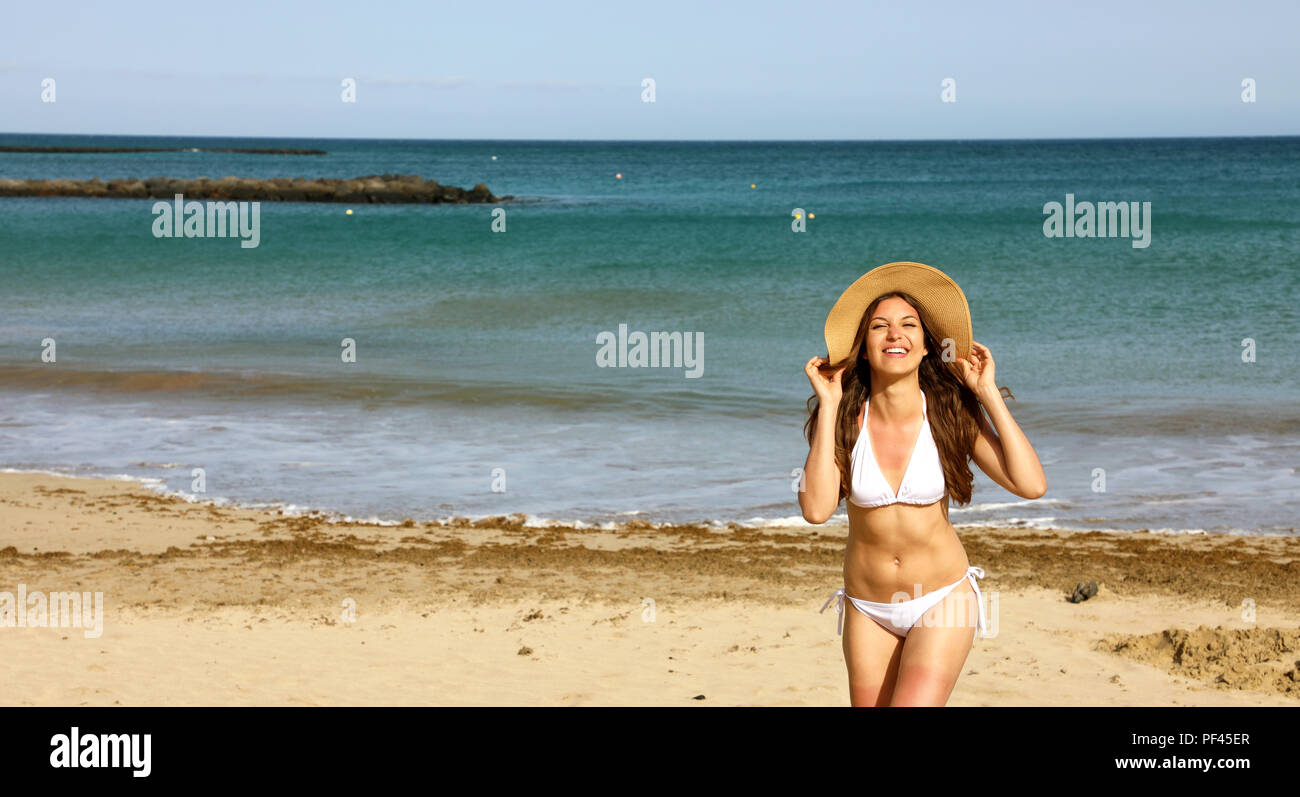 Beautiful bikini woman with straw hat enjoying ocean breeze at Lanzarote. Natural beauty girl looking to the sea relaxed in her Canary summer holidays - Stock Image