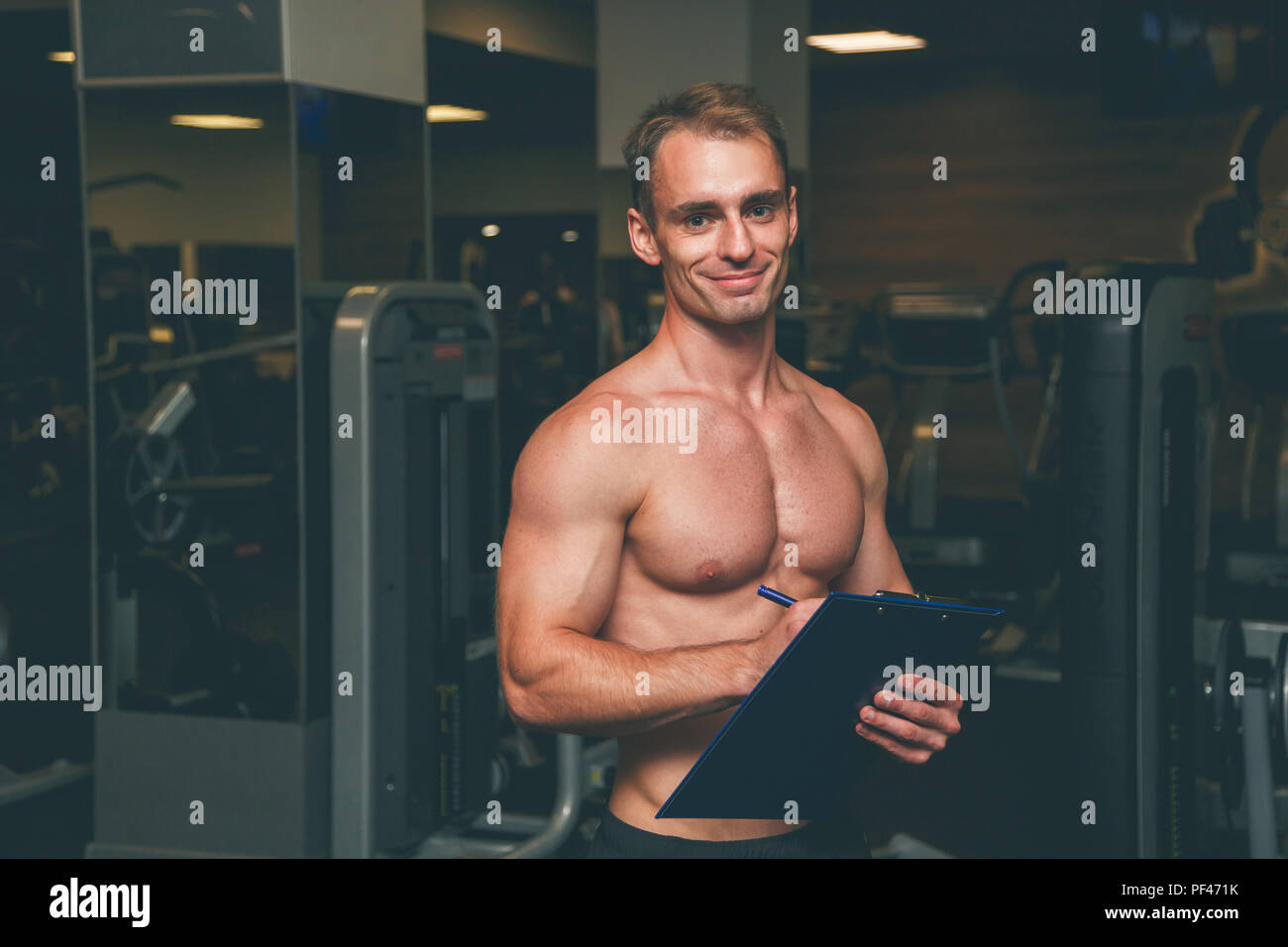 Personal Trainer, with a pad in his hand - Stock Image