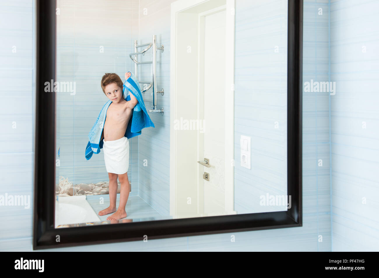 adorable healthy child dry off his body with blue towel in morning bathroom Stock Photo