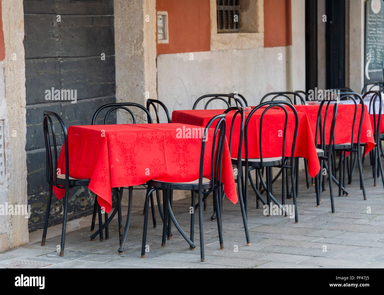 Bright red tablecloths on tables and chairs outside a restaurant in Venice Italy - Stock Image