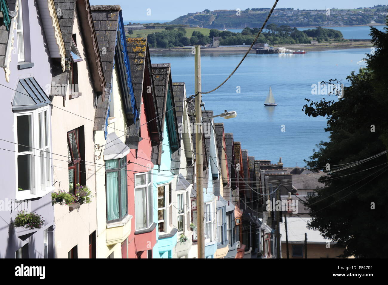 Colorful houses of Cobh, Ireland soaking the Irish summer sun. The symmetry is stunning and one of the best preserved parts in this little lovely town - Stock Image