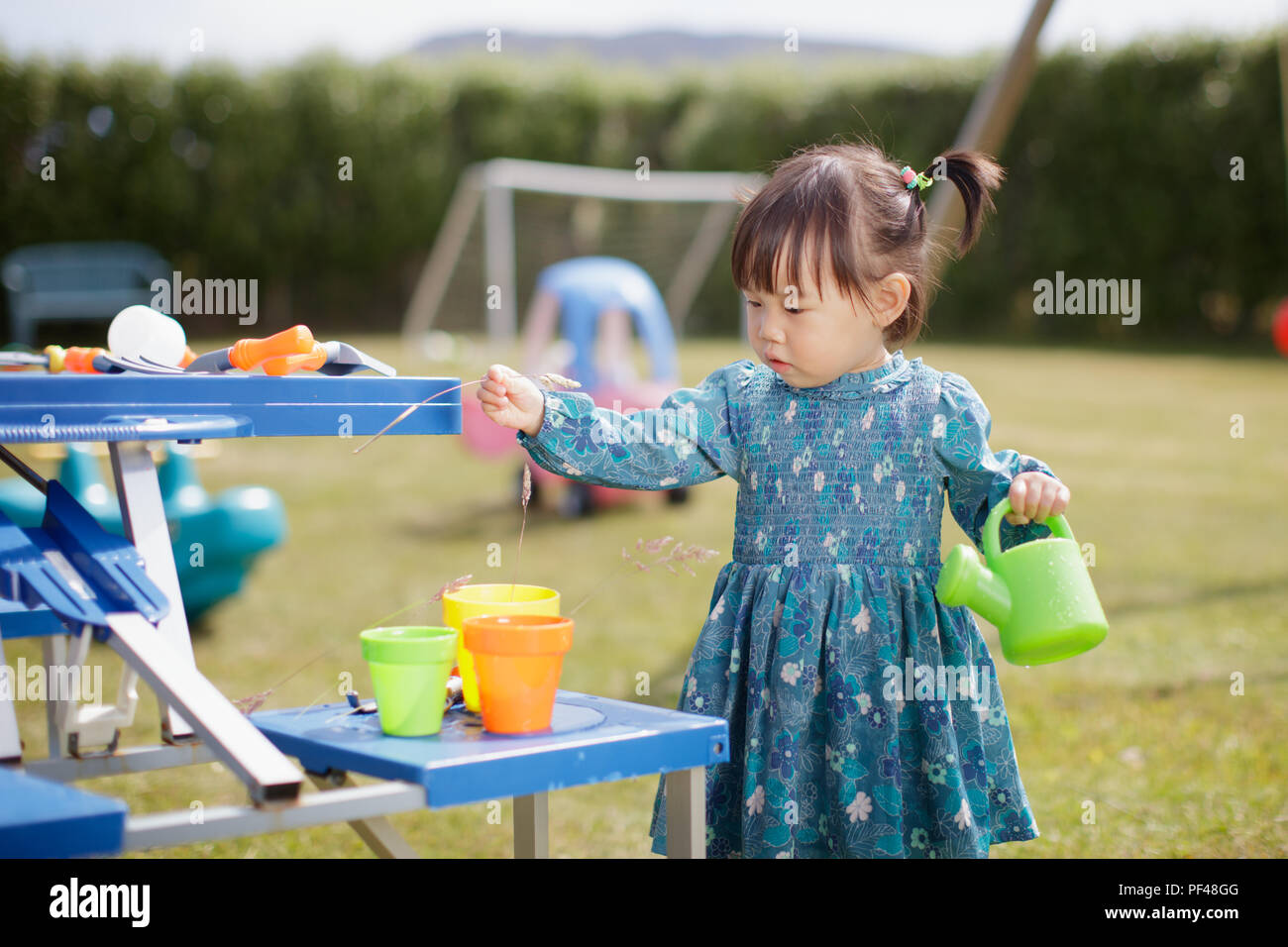 baby girl  pretend play in Summer garden - Stock Image