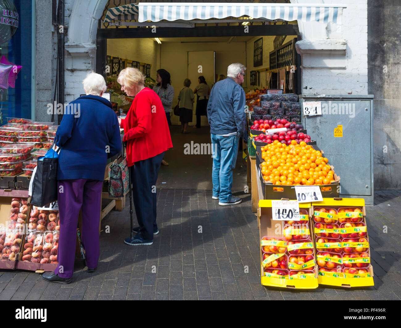 Customers at a greengrocer and fruiterers shop in an Archway in Middlesbrough Town Centre Stock Photo