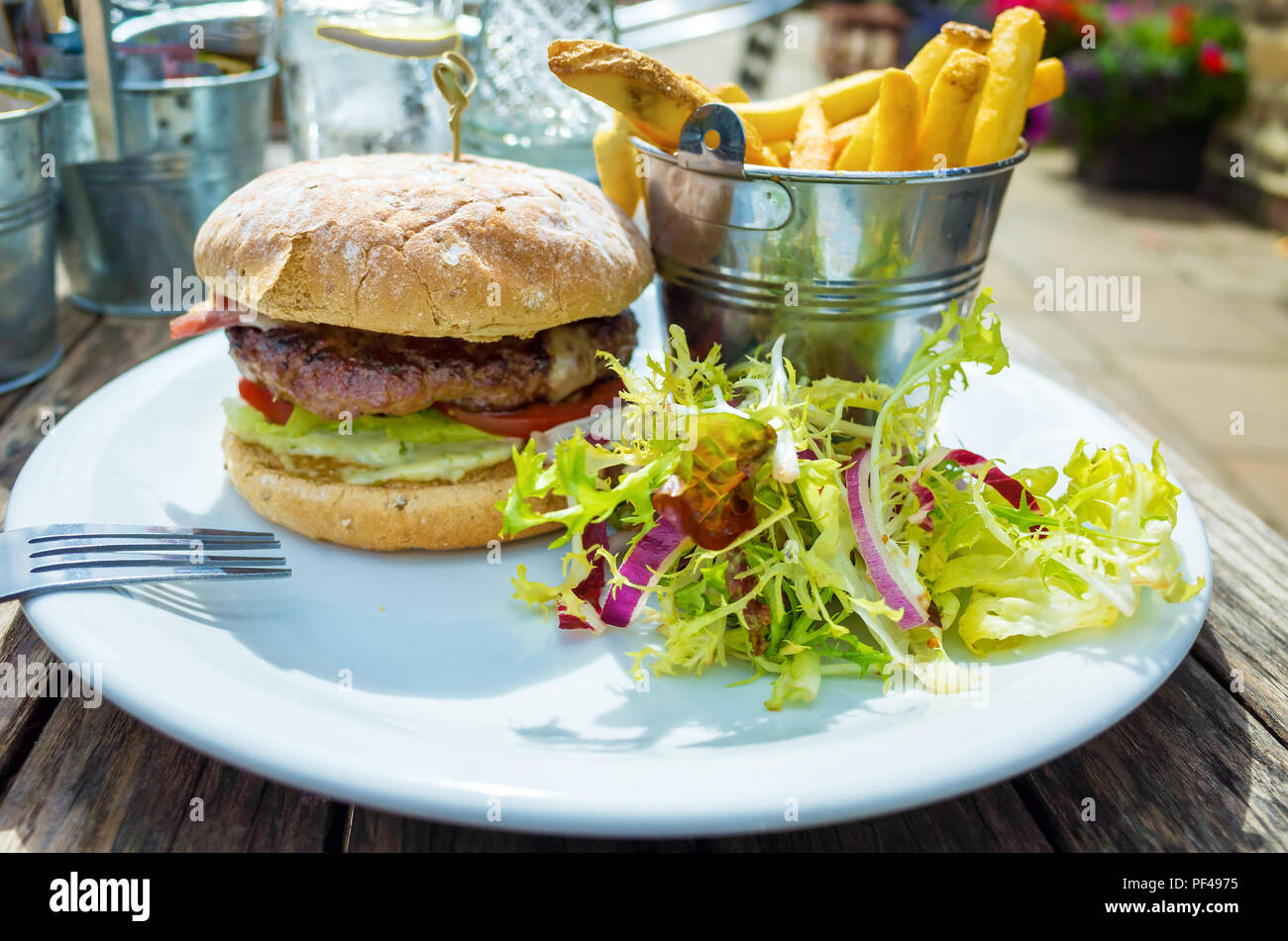 Café  lunch  a prime beef burger  with cheese bacon potato chips and salad Stock Photo