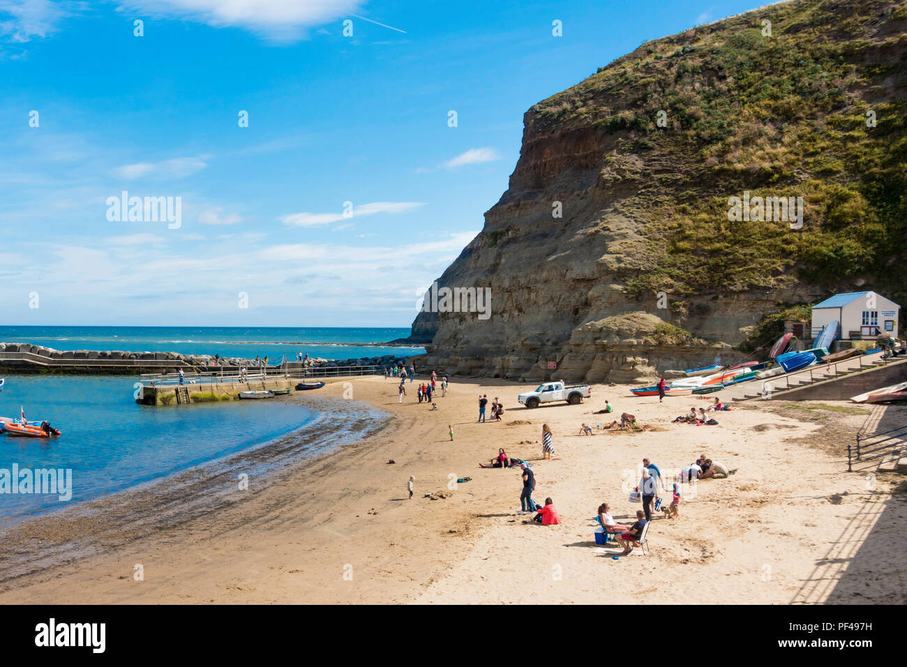 Holiday makers on the beach in the harbour at Staithes North Yorkshire UK on a warm summer day Stock Photo