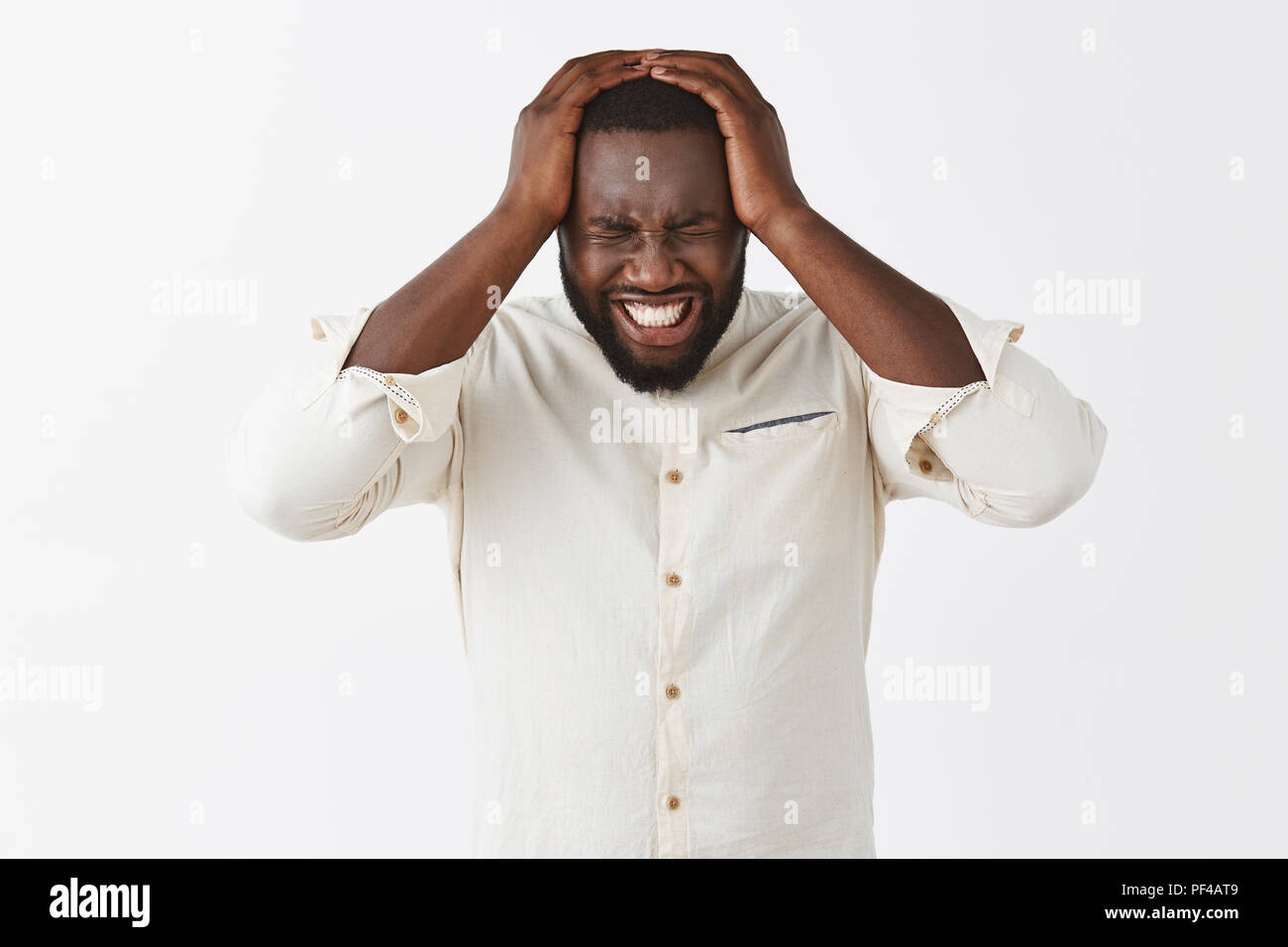 Cannot bear terrible headache anymore. Displeased intense suffering African American male in white shirt, grimacing, clenching teeth and closing eyes, holding hands on head, suffering mirgaine - Stock Image