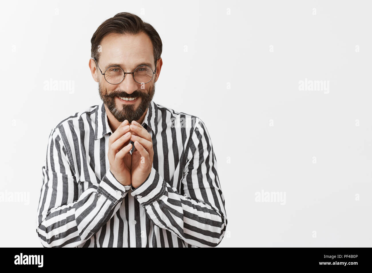 Excellent, everything goes by plan. Portrait of pleased grinning tricky man with beard and moustache having some intention in mind, steeping fingers and smiling with curious and mysterious expression - Stock Image