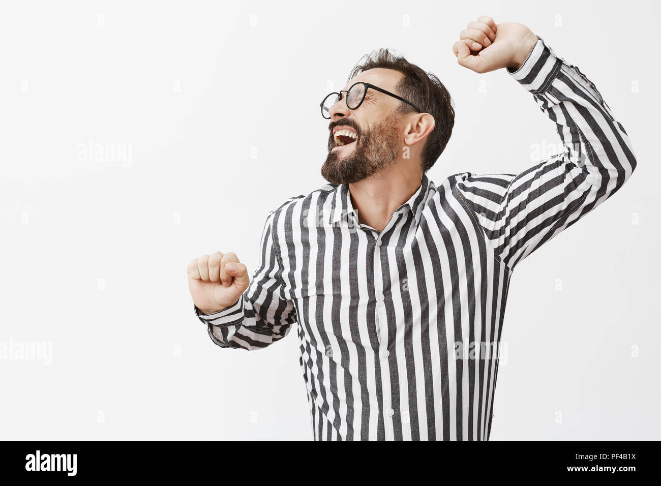 Happy tired man stretching while getting up from chair in office, going home. Portrait of exhausted funny adult man with dark short haircut and beard, pulling hands aside and yawning, feeling sleepy - Stock Image