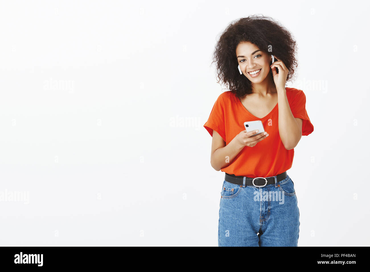 Best earphones ever. Positive carefree attractive woman with dark skin and afro haircut, wearing wireless earbuds, touching ear and holding smartphone while talking with friends with device - Stock Image