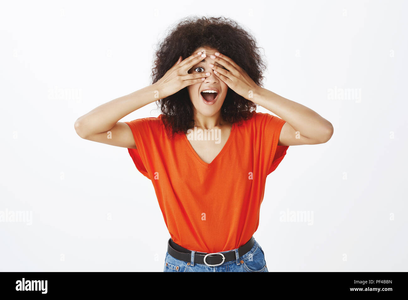 Girlfriend peeking impatiently waiting surprise. Portrait of good-looking happy woman with dark skin and afro hairstyle, covering eyes with palms and looking through fingers with opened smiling mouth - Stock Image