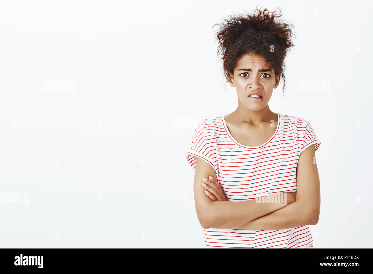 Studio shot of anxious cute dark-skinned woman in striped t-shirt, holding hands crossed on chest, frowning and grimacing while feeling worried and upset, nervous someone know secret - Stock Image