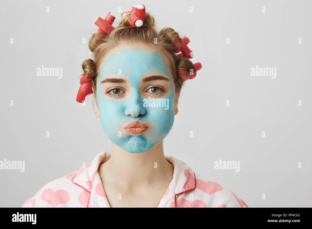 Studio shot of funny housewife in hair-curlers and nightwear, sulking while standing with facial mask and doing cosmetological procedures over gray background. Girl holds breath cause mask is stinky Stock Photo