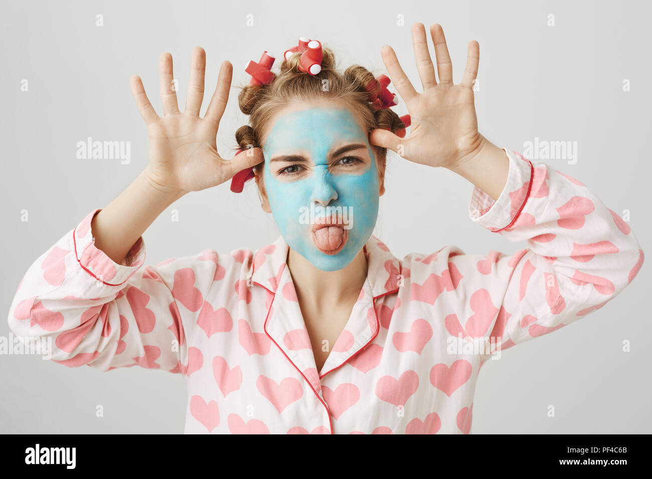 Playful and childish cute girl in facial mask and hair-curlers, wearing nightwear with heart print, making faces and sticking out tongue, being nasty while quarreling with sister over gray background - Stock Image