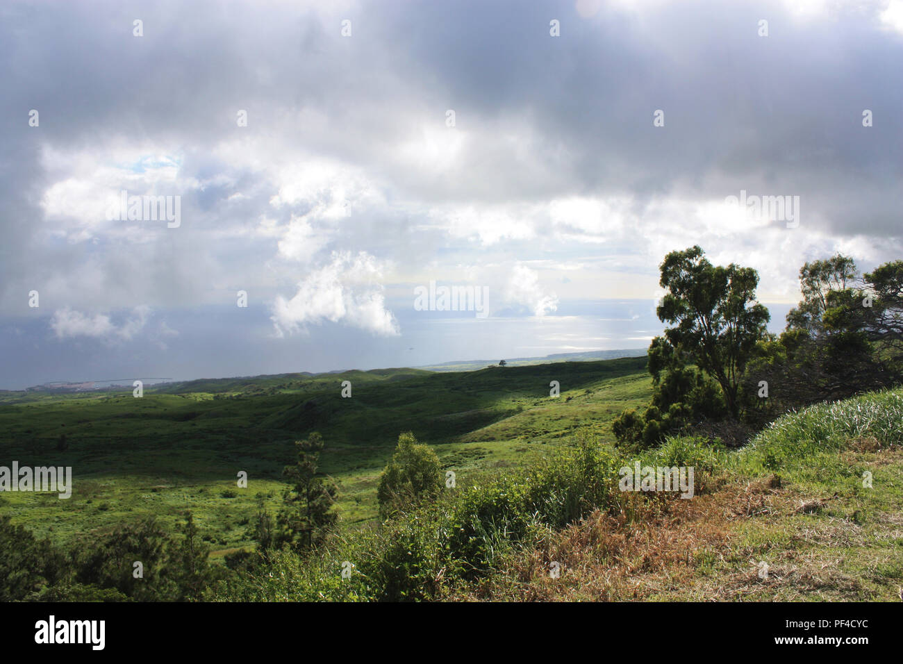 The rolling hills of pastureland in North Kohala, Hawaii, with low lying rainclouds casting shadows over the land and the Pacific Ocean in the backgro - Stock Image