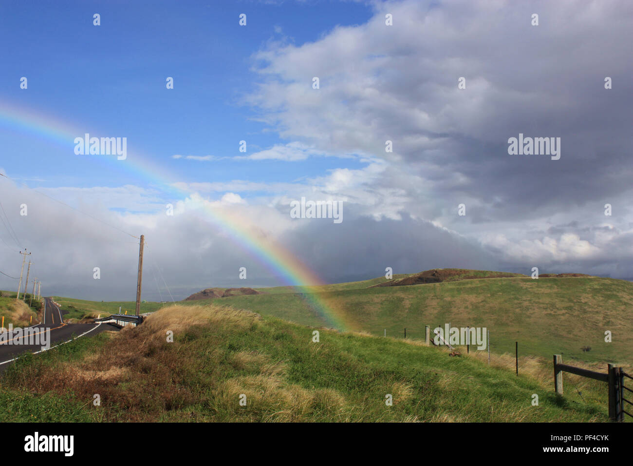 The end of the rainbow, dissolving into a grassy field next to the Kohala Mountain Road in North Kohala, Hawaii, USA - Stock Image