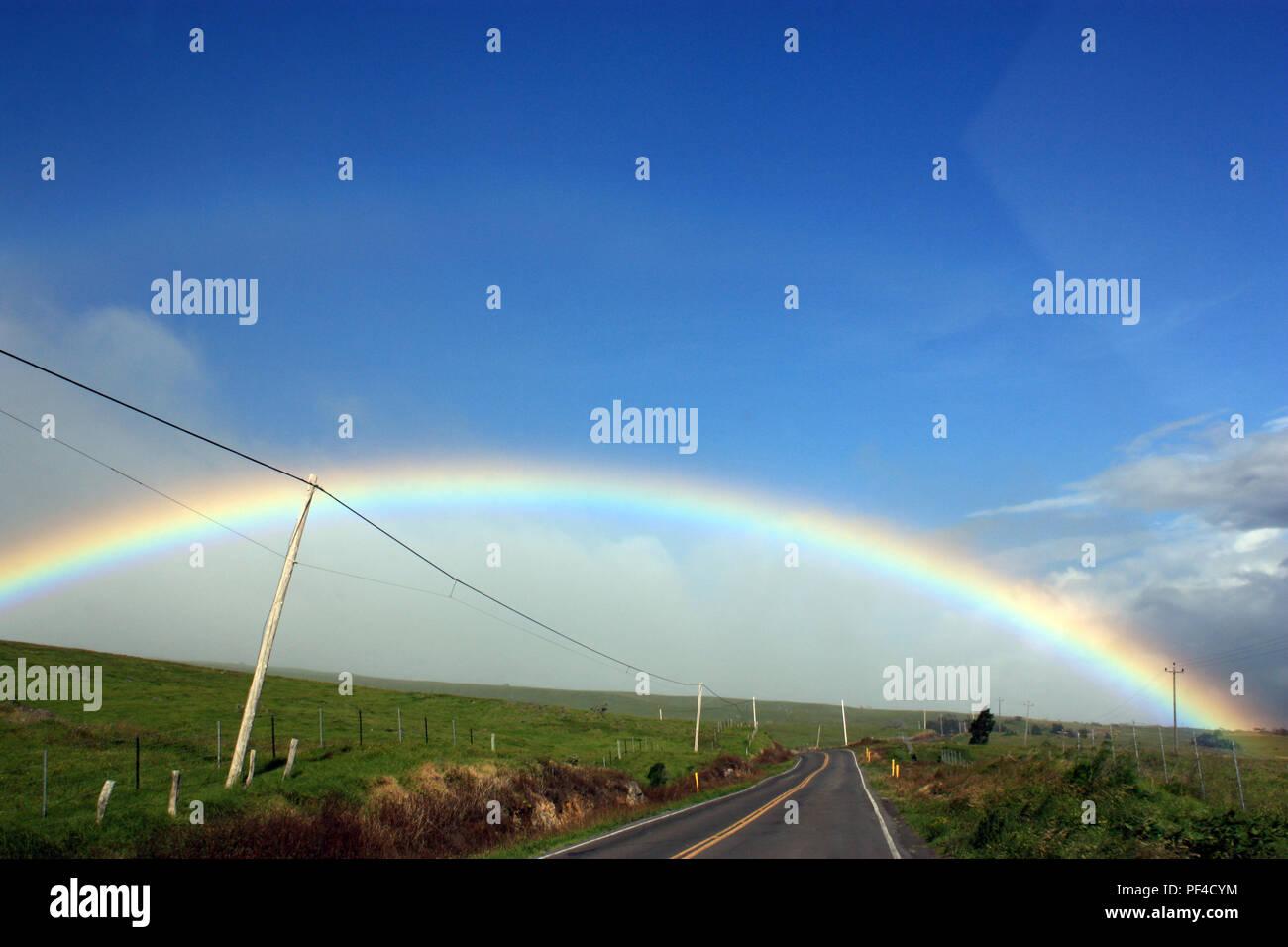 A rainbow crossing the Kohala Mountain Road in North Kohala, Hawaii, USA - Stock Image
