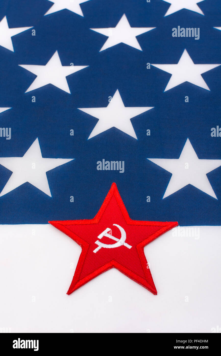 Red Star Hammer and Sickle badge with US / American Stars and Stripes flag. Metaphor US Radical Left, Activism, Democratic Socialists, US Elections. - Stock Image