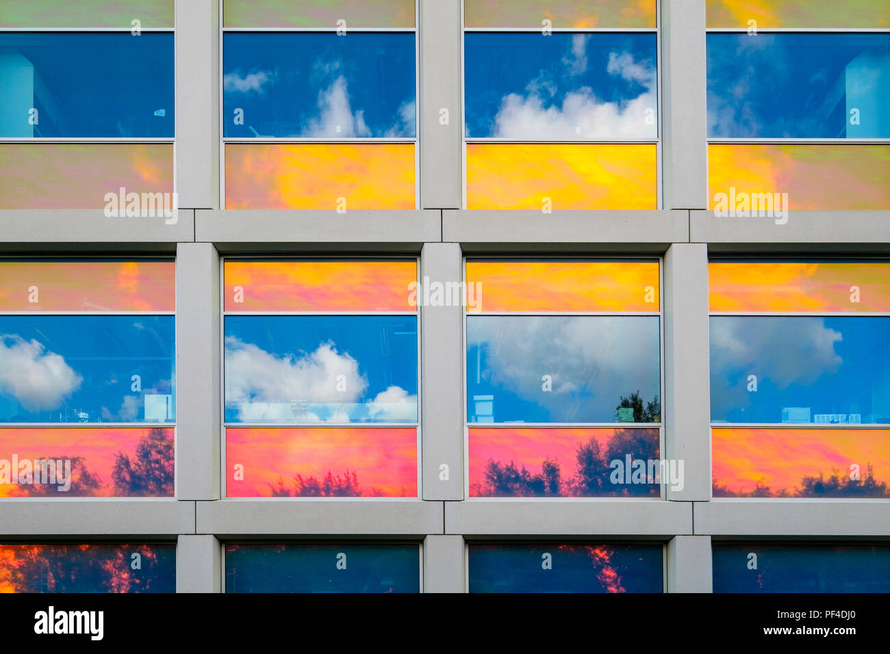 Reflections in colorful coated windows - Stock Image