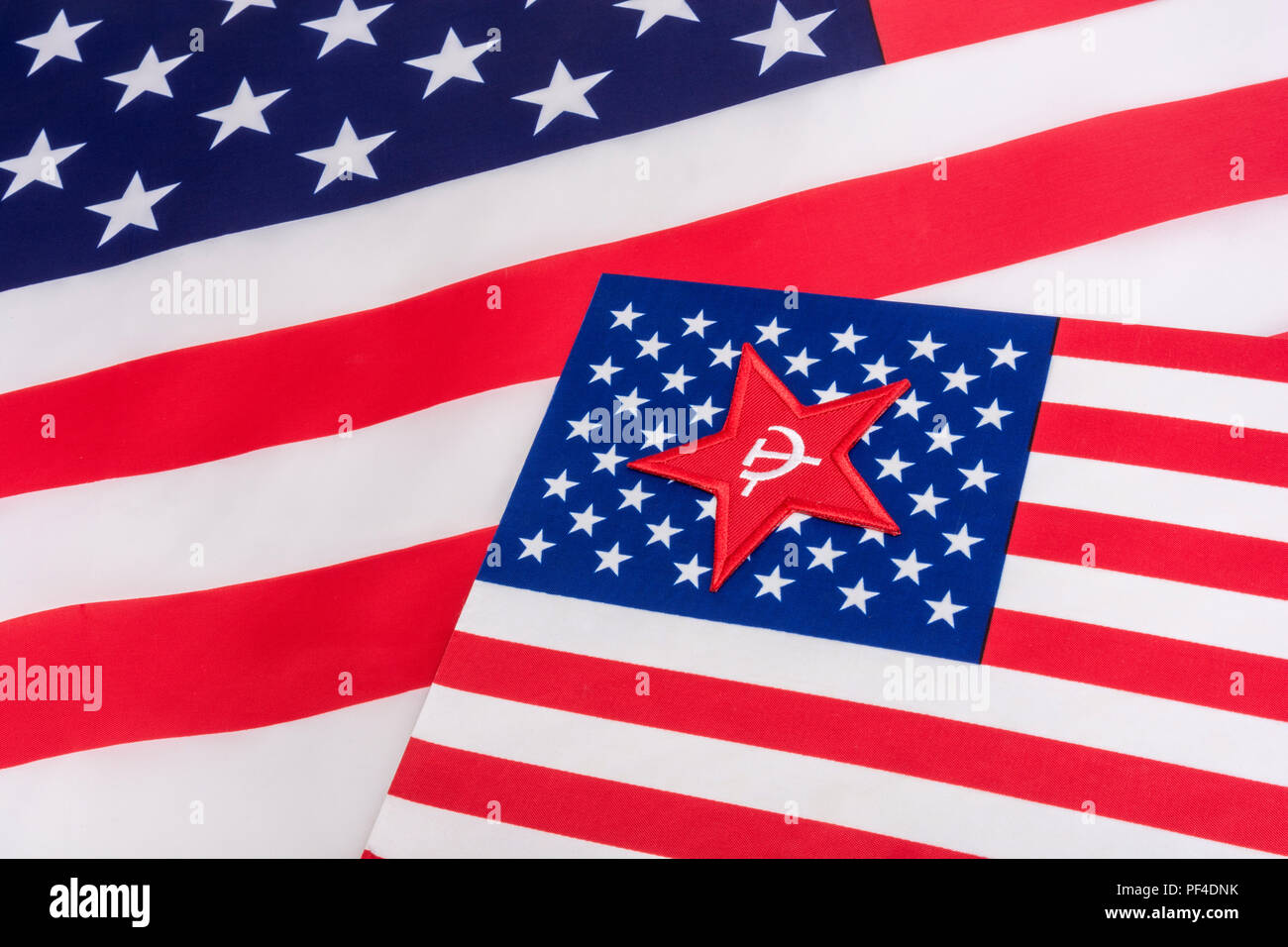 Red Star Hammer and Sickle badge with U.S / American Stars and Stripes flag. Metaphor U.S Radical Left, Activism, Democratic Socialists, US Elections. - Stock Image