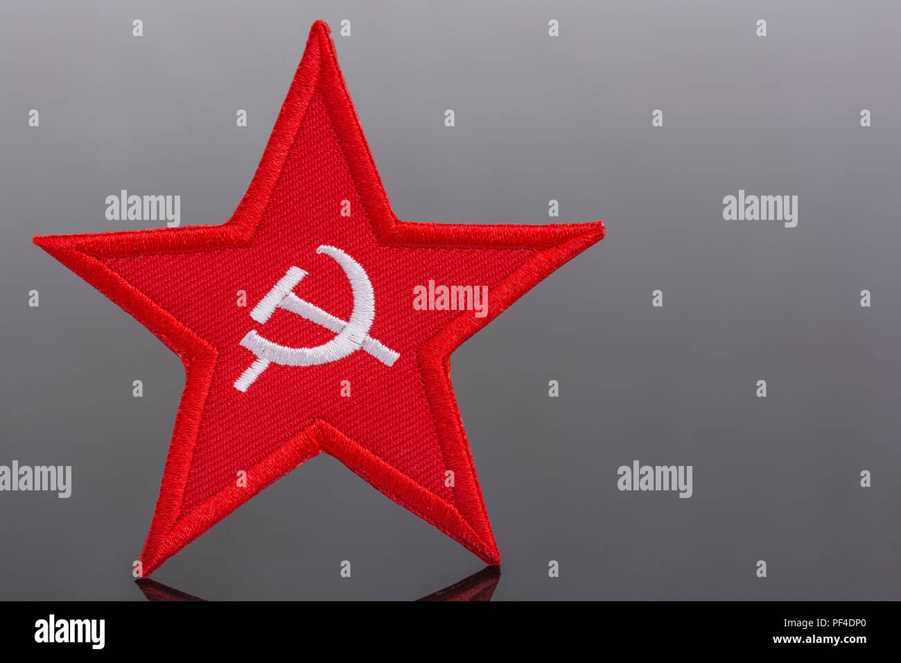 Red Star Hammer and Sickle badge with US / American Stars and Stripes flag. Metaphor US Radical Left, Activism, Democratic Socialists, US Elections. Stock Photo