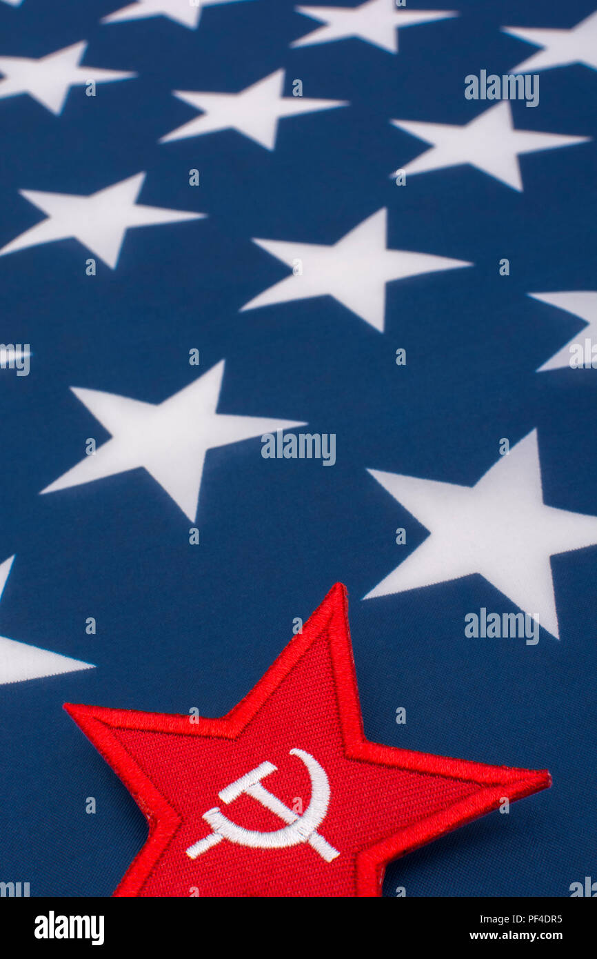Red Star Hammer and Sickle badge with U.S / American Stars and Stripes flag. Metaphor U.S Progressives, Activism, Democratic Socialists, US Midterms, - Stock Image